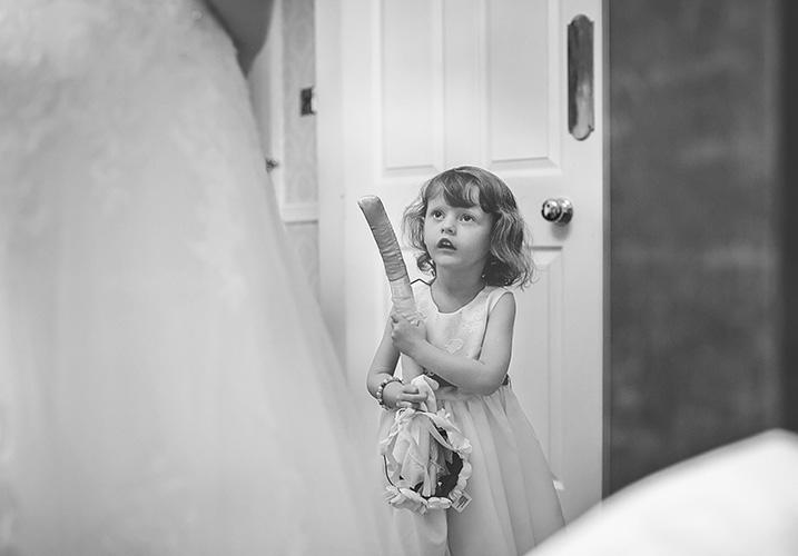 Daughter watching her mum put on her wedding dress