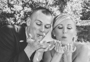 blowing confetti on wedding day photo