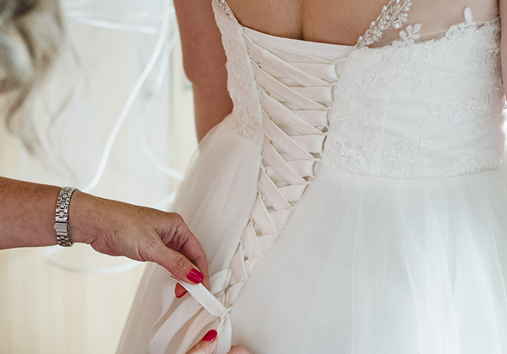 bride being laced into her wedding dress