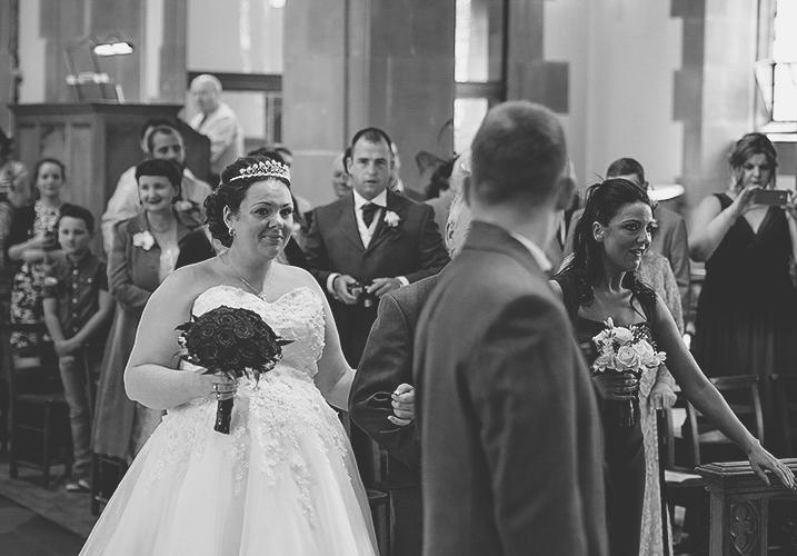 bride walks down the aisle in a church