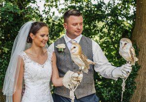 couple holding a barn owl