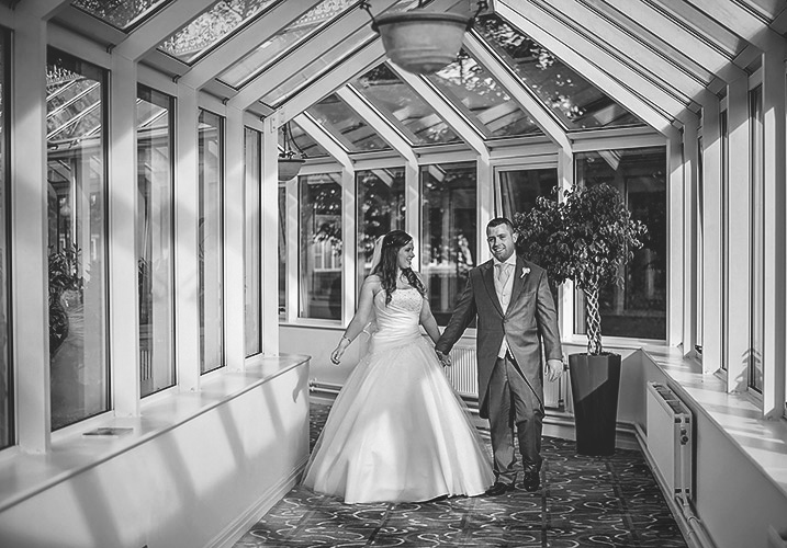 Bride and groom walking through the conservatory